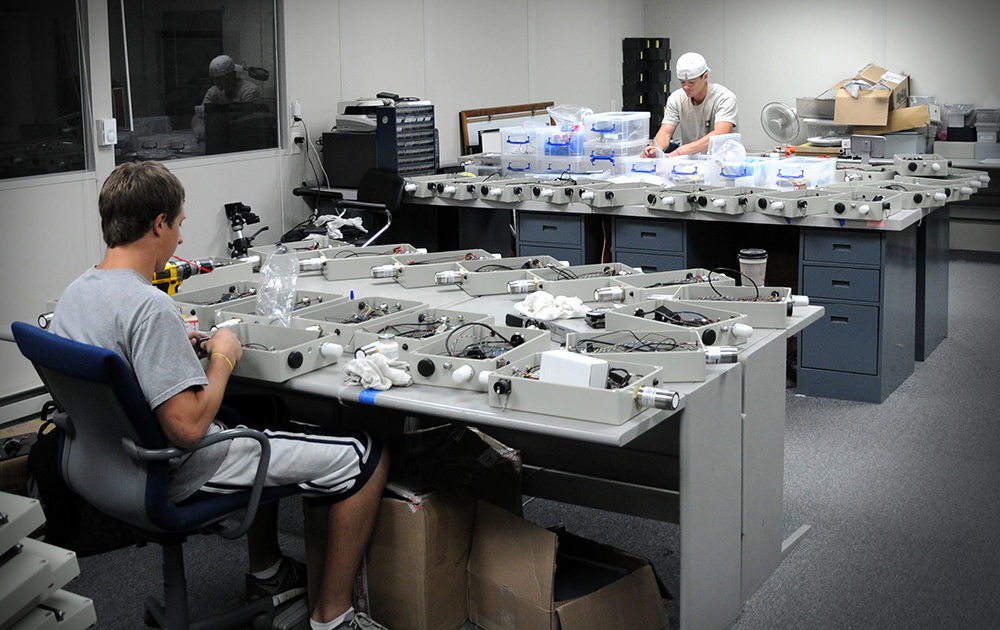 Students work in the IIHR Electronics Shop, assembling stream-stage sensors.