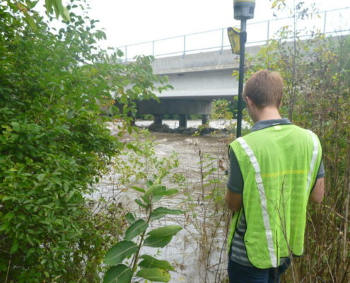 IIHR staff member conducting fieldwork in a floodplain.