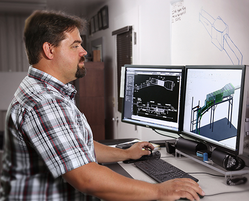 A man stands at a computer using design software.
