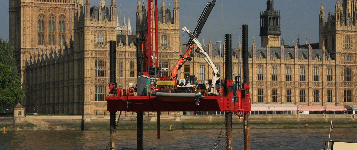 Construction equipment in the river near the British Parliament.