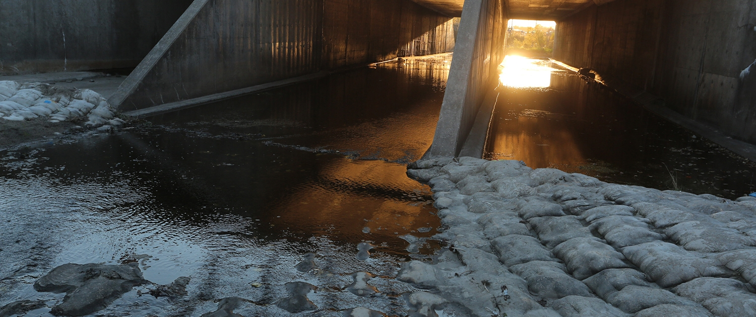 Morning sunlight floods a view of a three-box self-cleaning culvert.